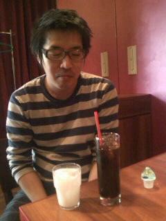 話に夢中になり、間違ってコーヒーフレッシュをコップの水に入れてしまった智六師の図。