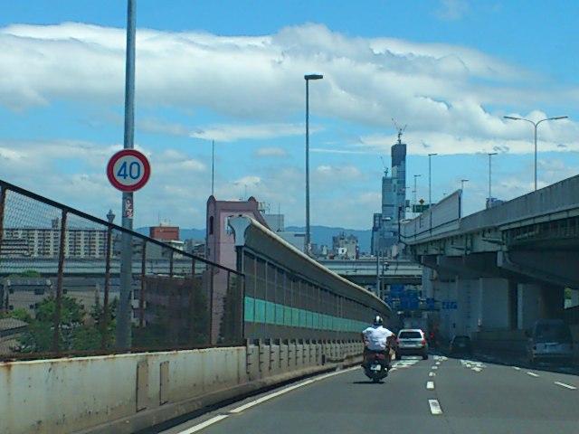 阿倍野ハルカスと通天閣を撮影。通天閣は速度標識のすぐ左、風景と同化してます。。ハルカスでかいなあ。